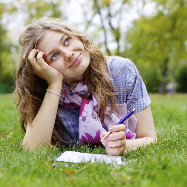 teenage girl making homework in park